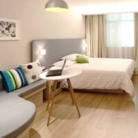 A Airbnb apartment with simple furnishings and the text how to get long term airbnb guests.