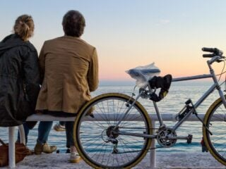 Travelers sitting on a bench near water with a bicycle nearby.