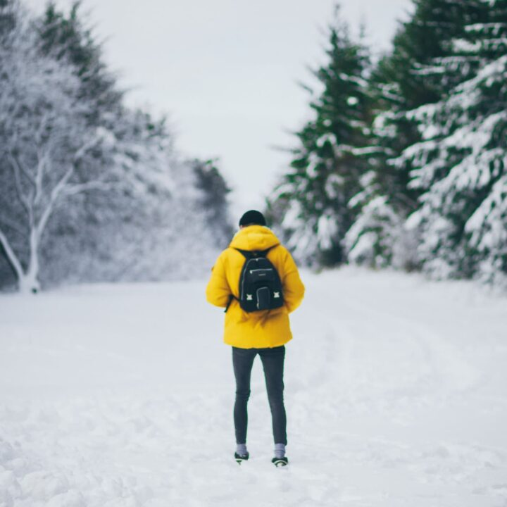 Man in yellow jacket alone in the snow - If you find yourself planning to spend Christmas solo, consider booking a ticket to these destinations for a Christmas solo travel adventure.