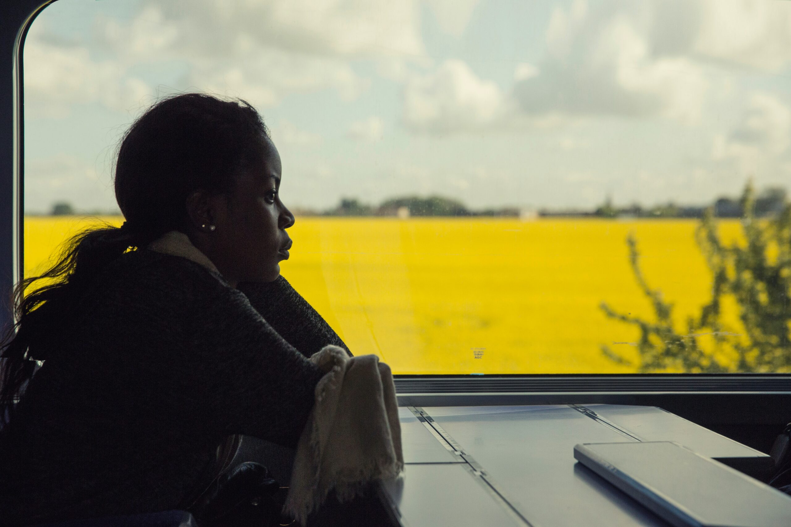 A woman sits on a train and stares into space demonstrating what burnout can look like for some people.