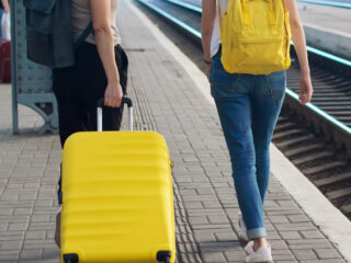 Two women walking in a train station, one woman is rolling a yellow suitcase and the other woman is carrying a yellow backpack.