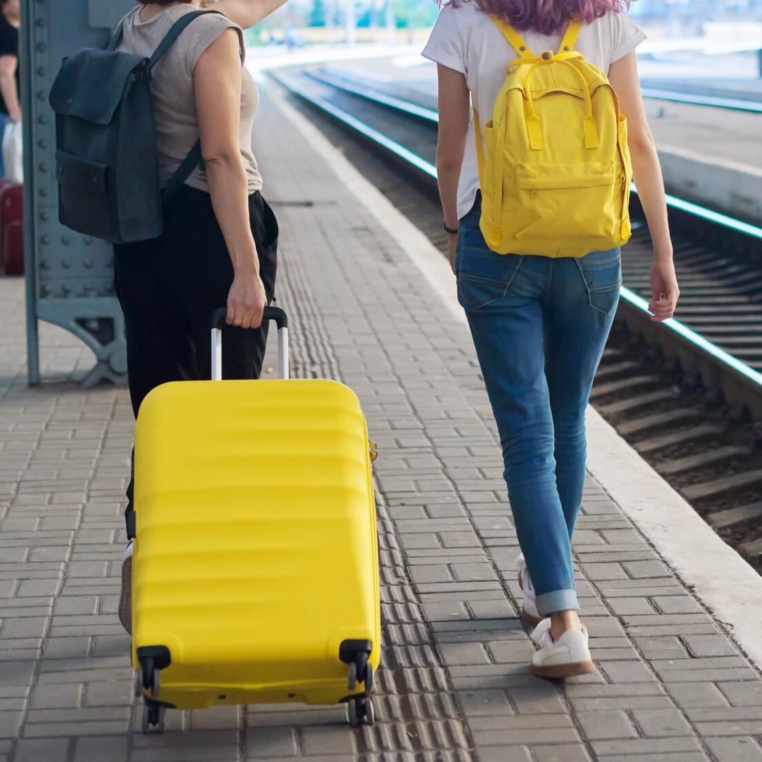 Two women walking in a train station, one woman is rolling a yellow suitcase and the other woman is carrying a yellow backpack, illustrating that even shy travelers need someone to talk with about travel.