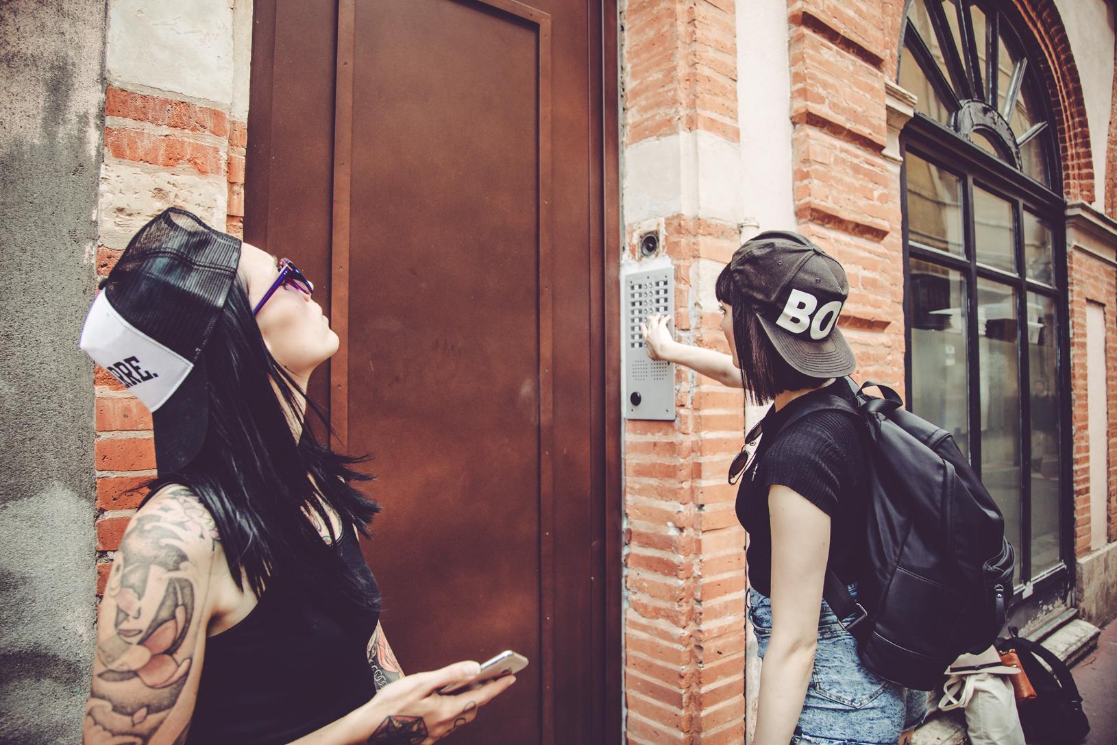 Two women ringing a doorbell.