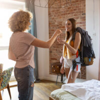 A woman hands keys to another woman in a bedroom.