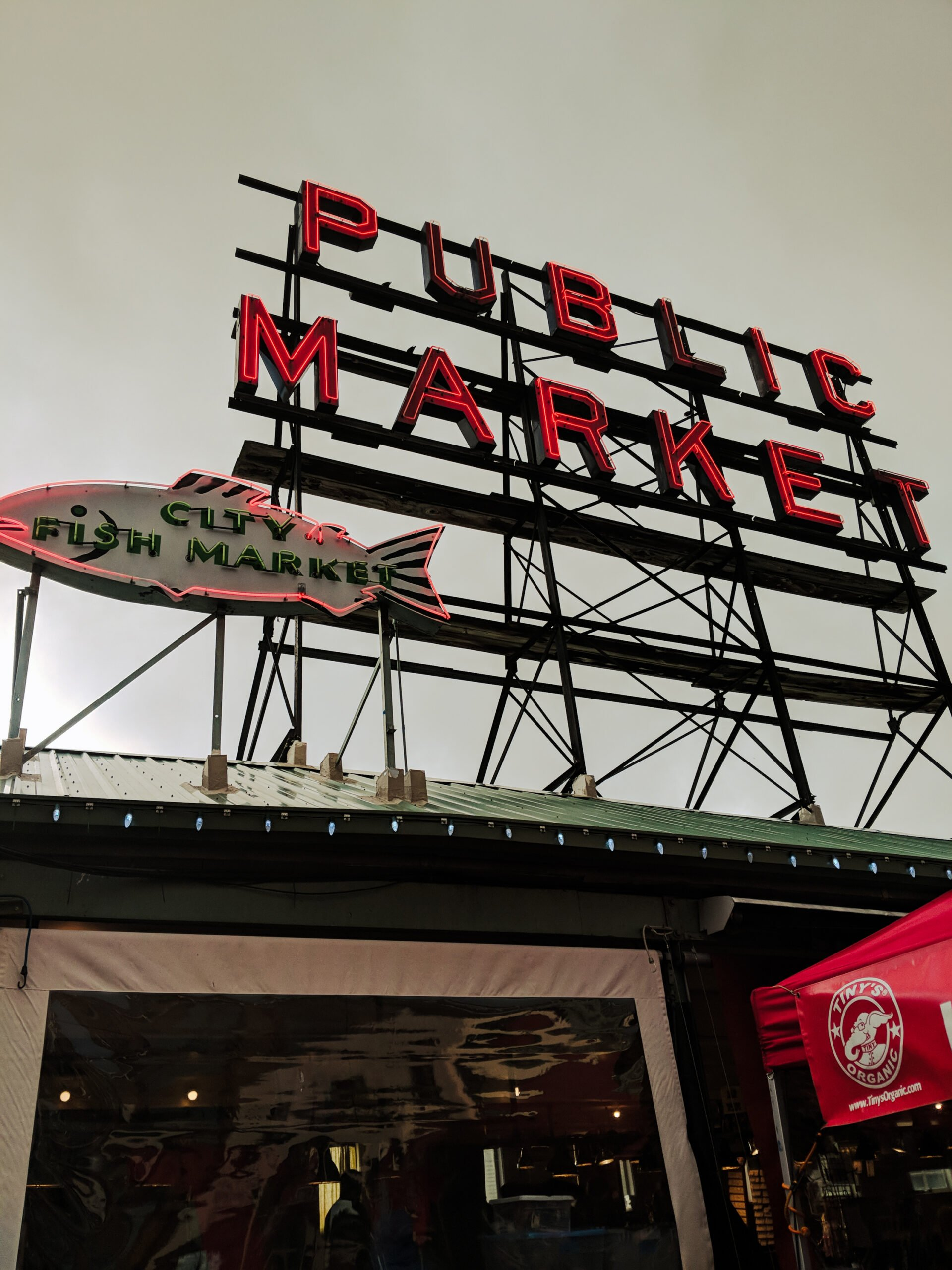 A neon sign at pike place market on an overcast winter day.