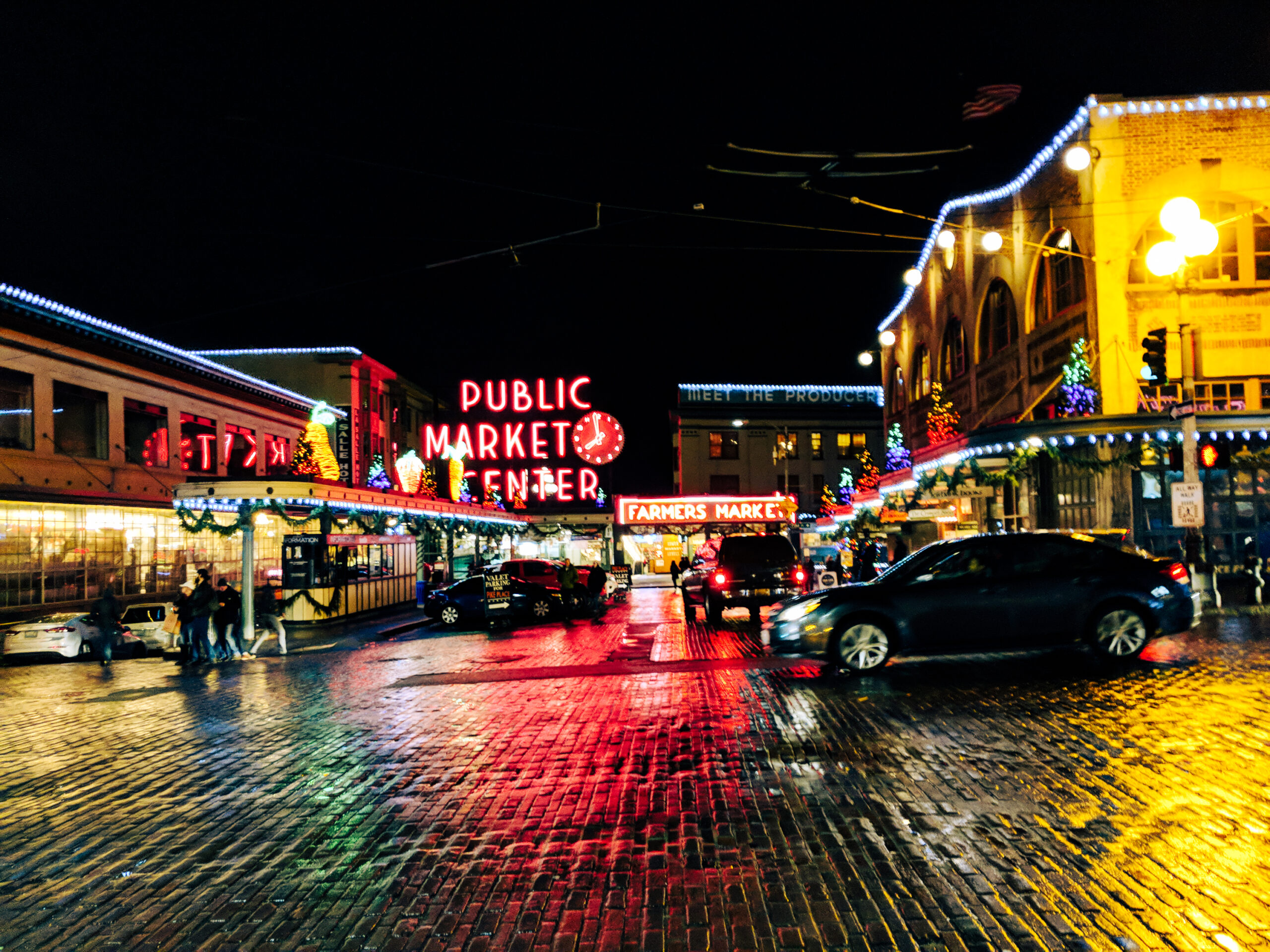 Pike place market at christmas after dark, with car driving past.
