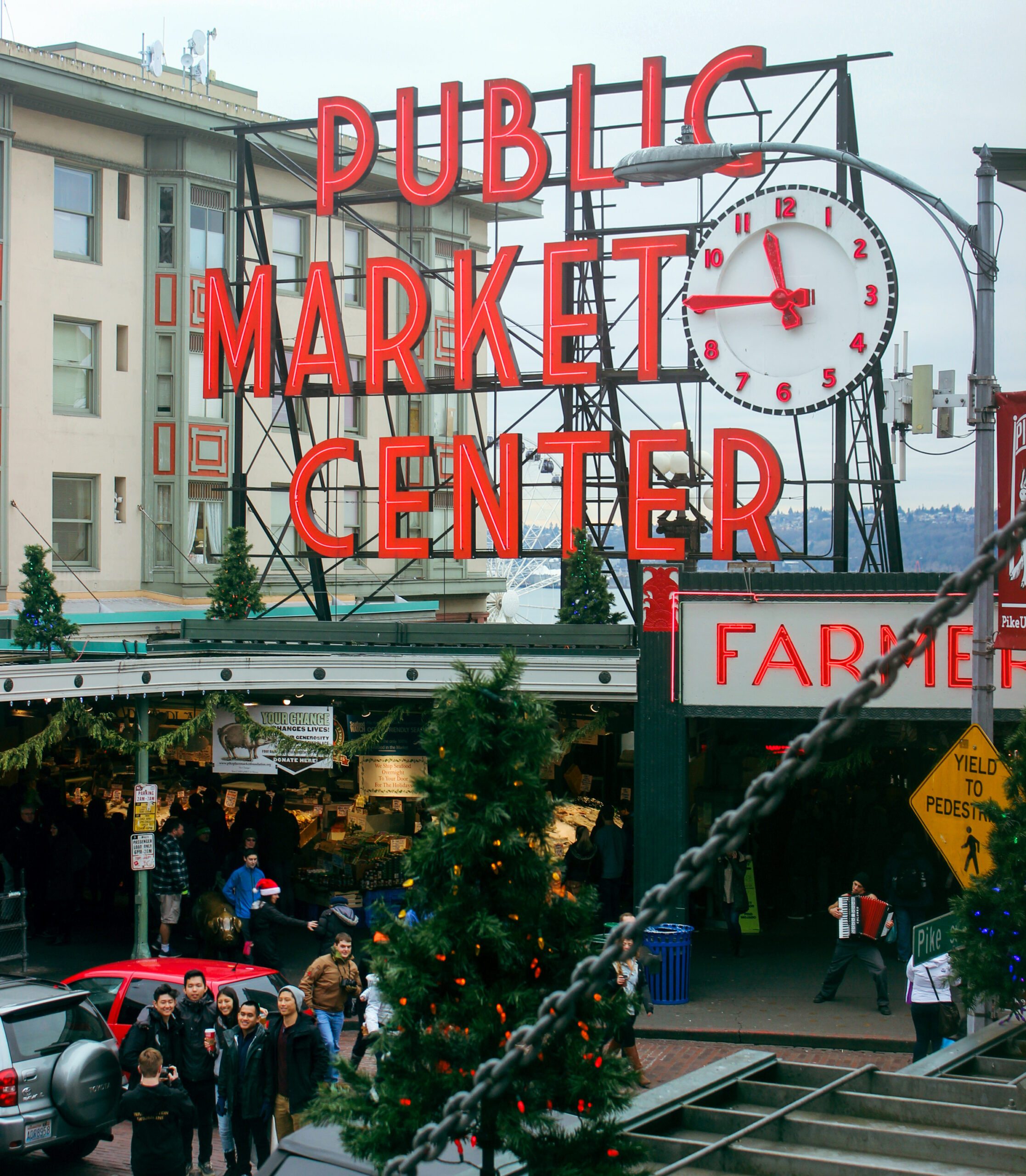 A photo of the main entrance of pike place market, showing christmas decorations, a group posing for a photo, a dancing accordion player, and the iconic neon sign.