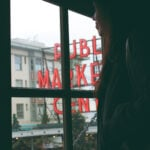 A woman looks out a window at the pike place market sign and christmas decorations