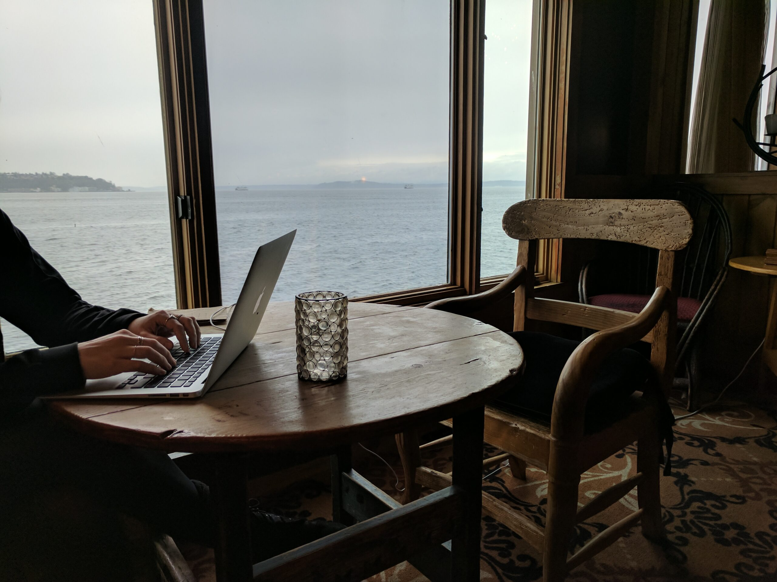 A table at the edgewater hotel, in front of a window with a elliott bay view.