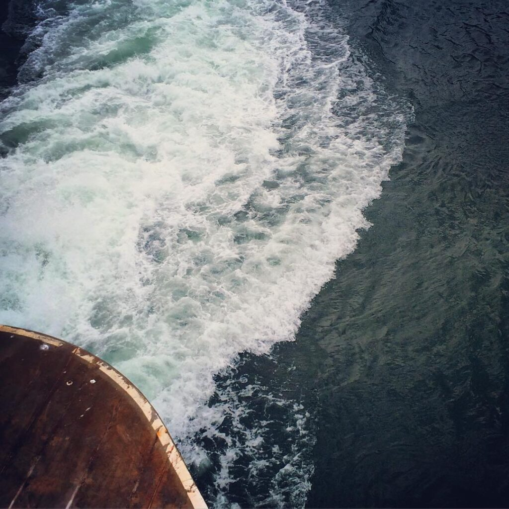 The wake behind a washington state ferry crossing the puget sound.
