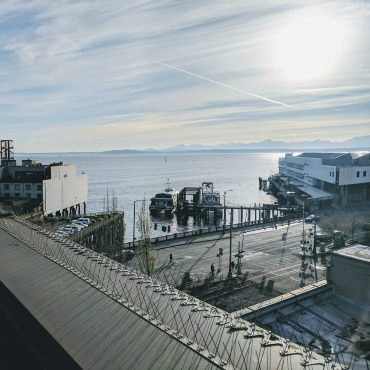 View of the Clipper Ferry terminal in seattle, with boat preparing to leave for Orcas Island, mountains behind.