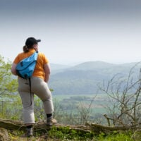 A plus size traveler in an orange shirt at an overlook.
