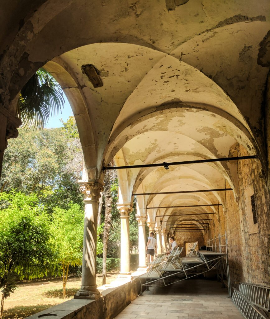 Arches of a monastery surrounding a courtyard with an orchard.