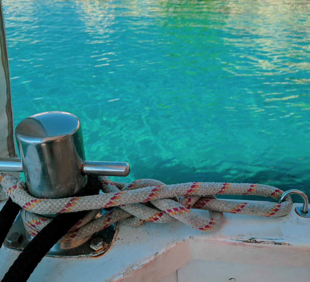Turquoise blue waters shown behind nautical ropes.