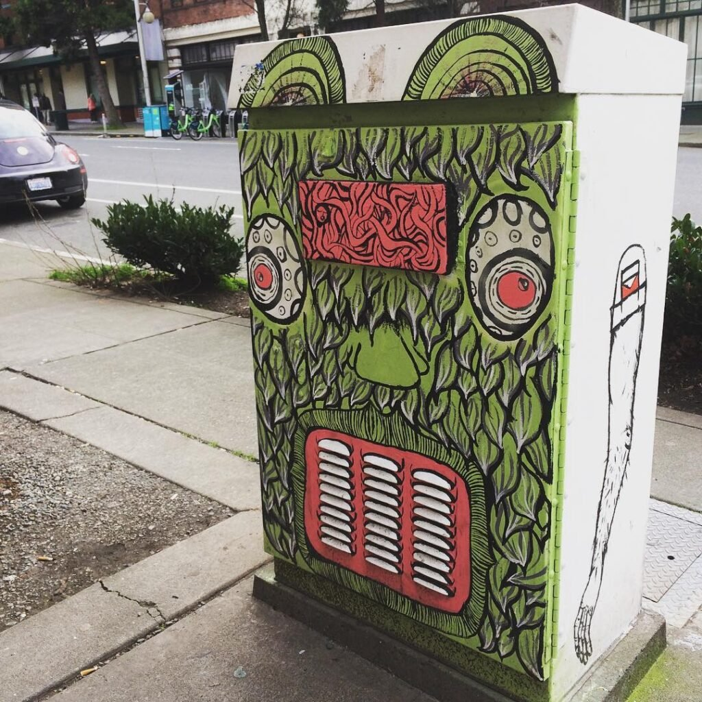 This painted utility box, depicting a green mythical creature, is one of a number of smaller street murals in seattle.