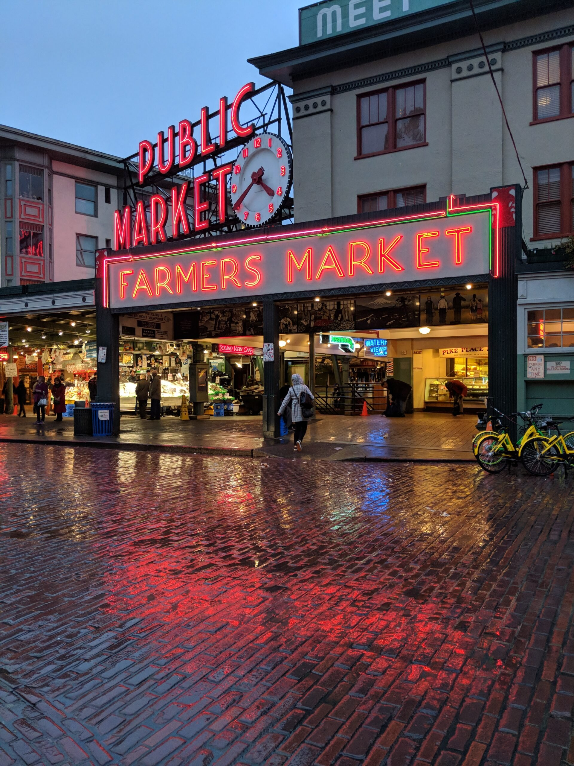 Neon signs illuminated in the rain at pike place market.