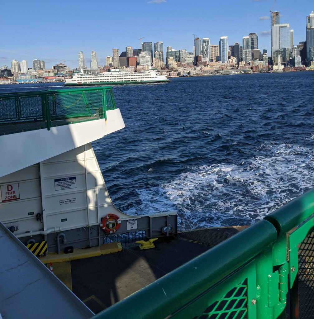 Washington state ferry leaving seattle bound for bainbridge island, with the seattle skyline in the background.