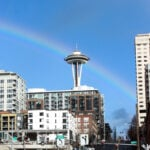 A rainbow behind the space needle as seen from the waterfront in seattle.