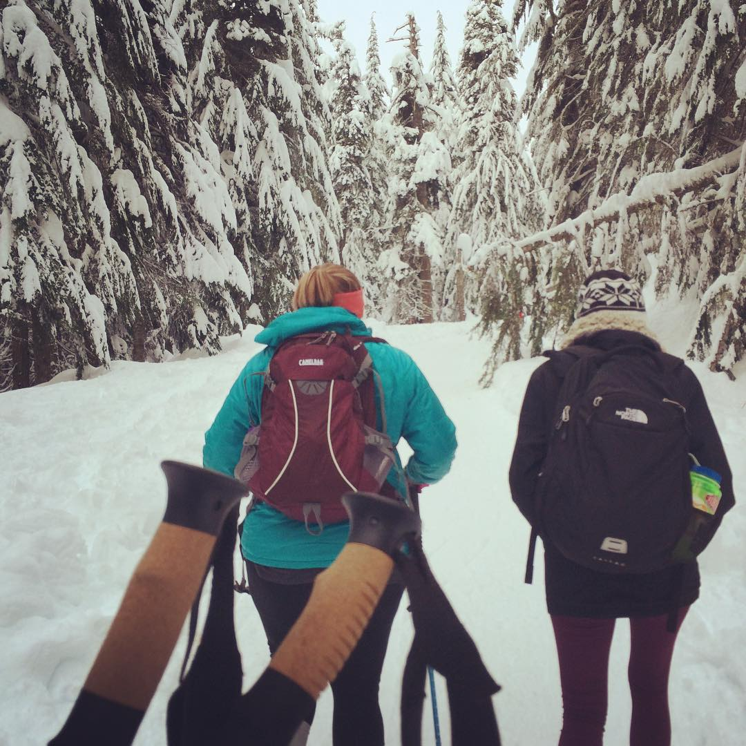Two women hiking into a snow-covered woods.