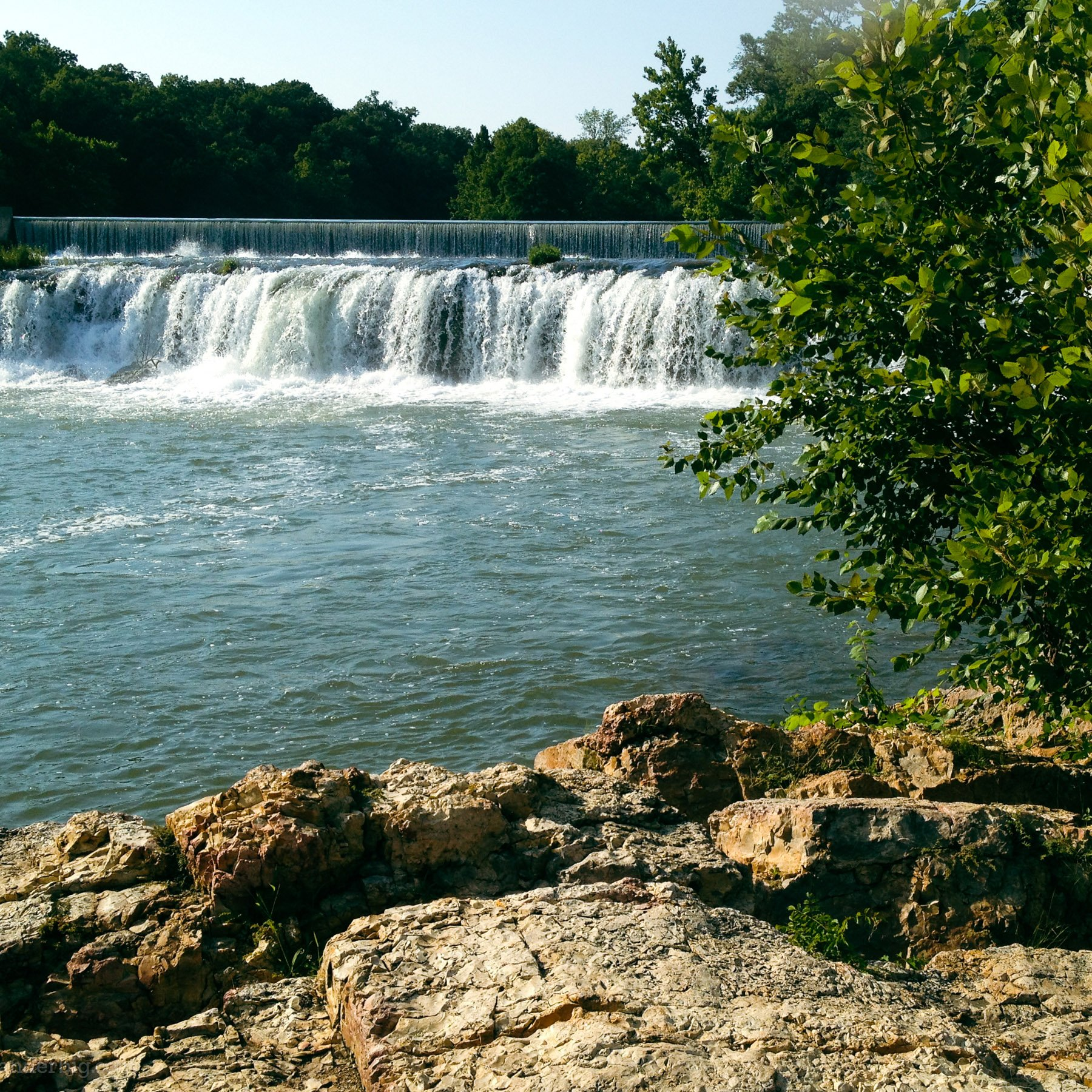 Water from shoal creek flow over the chert rock formation making up grand falls waterfall, near joplin, mo.