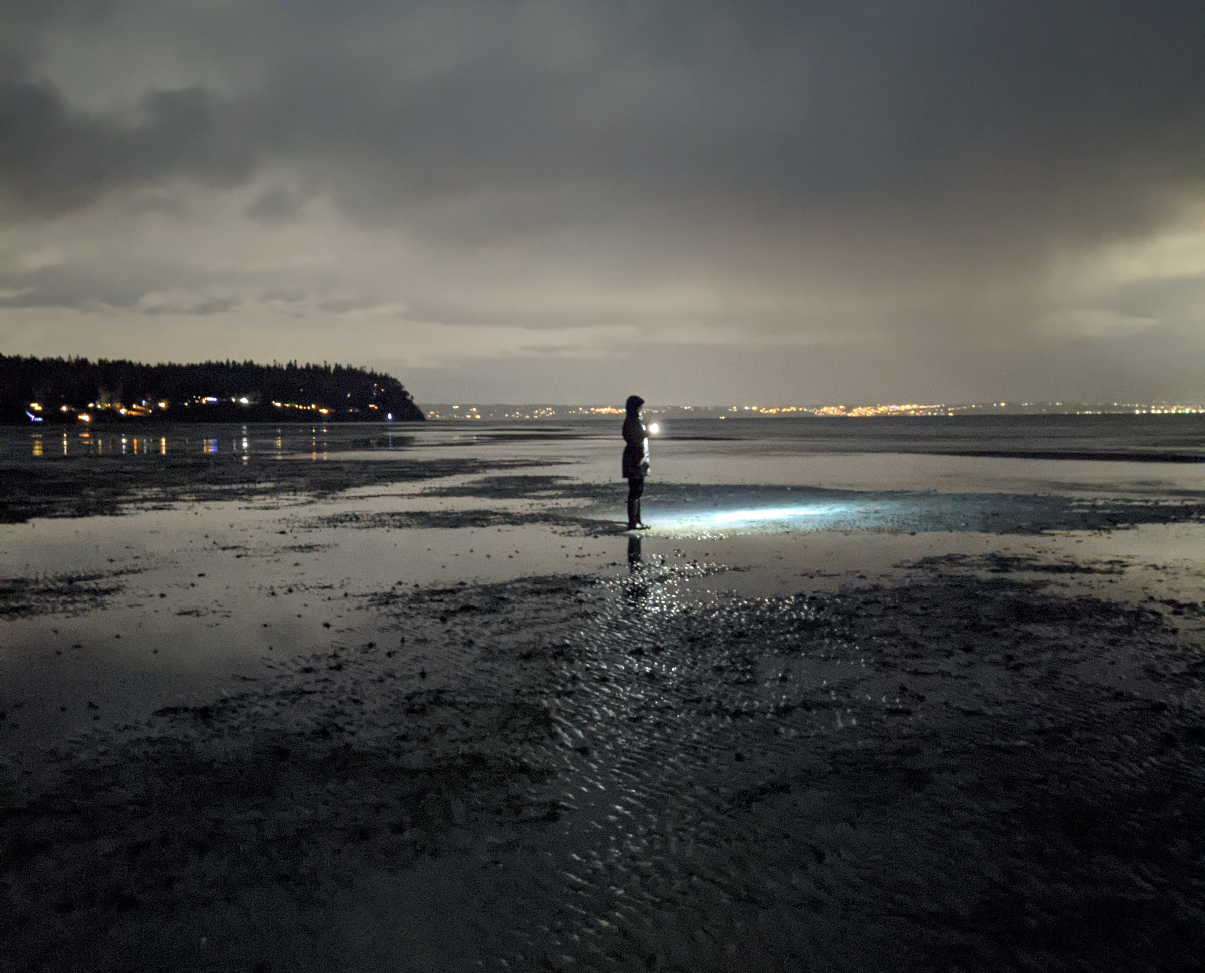 A person stands on tight flats in the dark with the city of seattle in the background