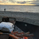 Hot dogs cook over a fire pit on a beach in the pacific northwest.