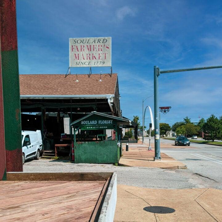 Soulard Market in Saint Louis, Missouri, with gateway arch in backdrop.