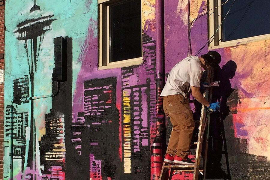 A man painting a mural of seattle