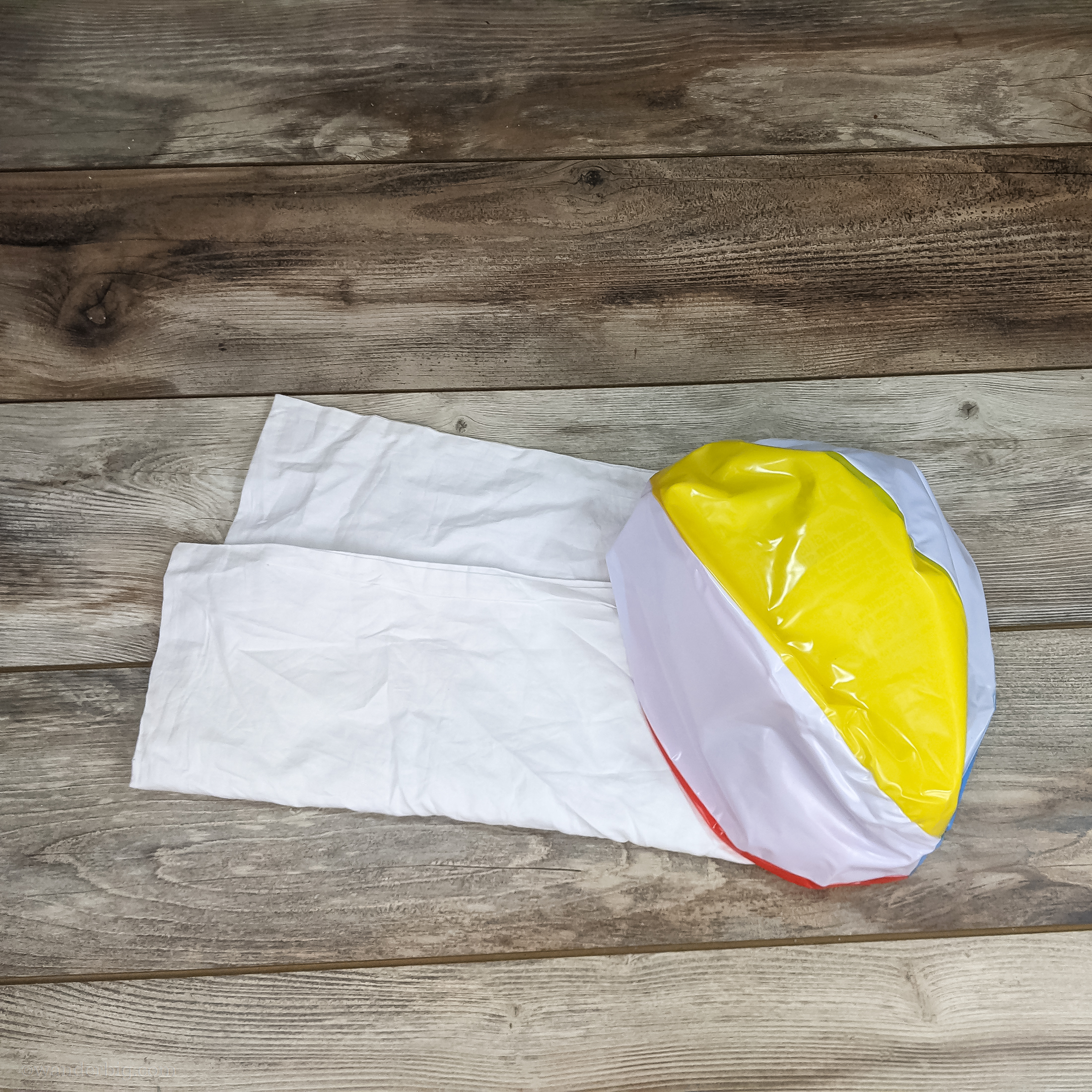 This image shows the two items you'll need to make a diy travel pillow: a zippered pillowcase and a uninflated beach ball.