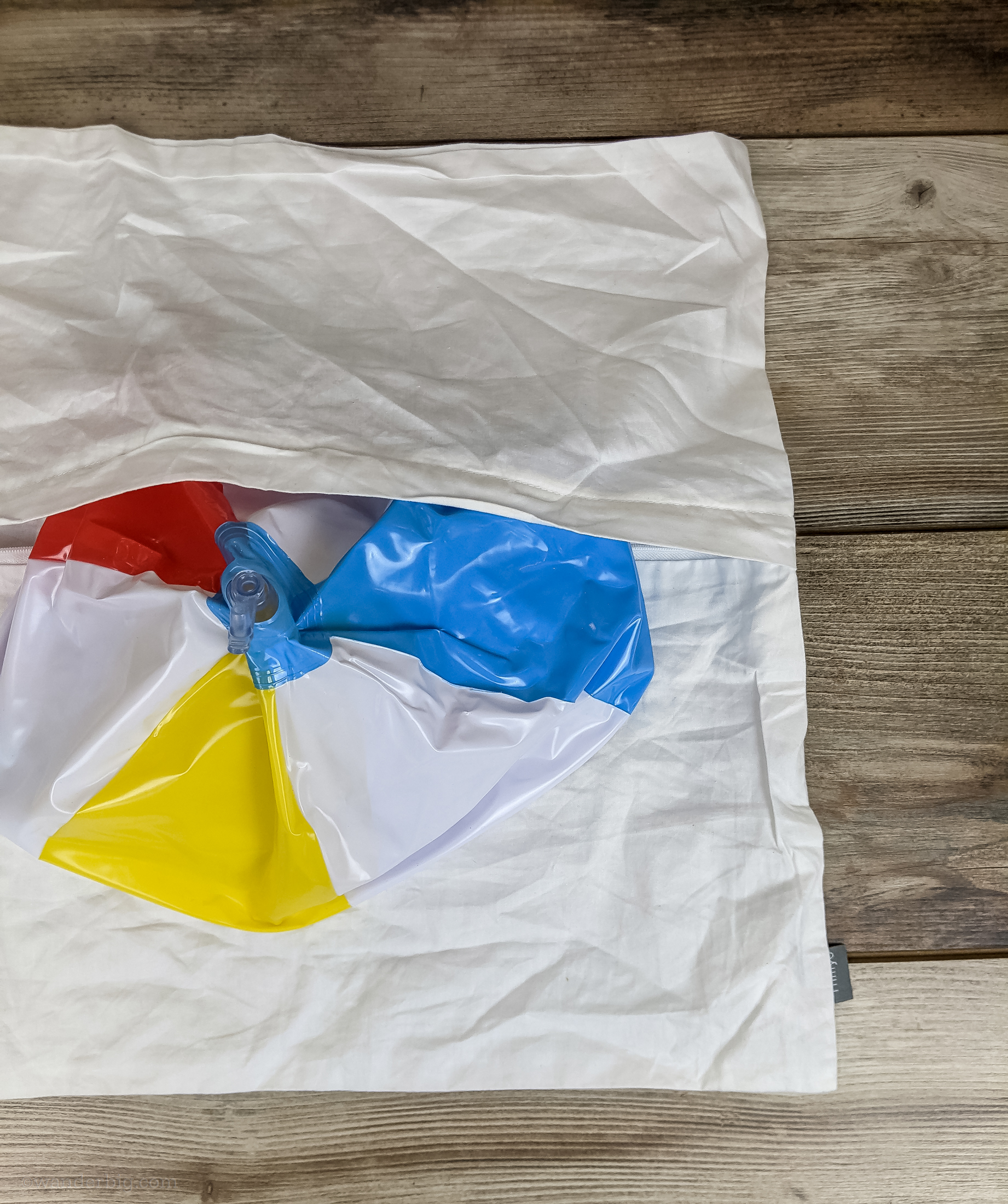 An uninflated beach ball being inserted into a cotton pillowcase to form a diy travel pillow.