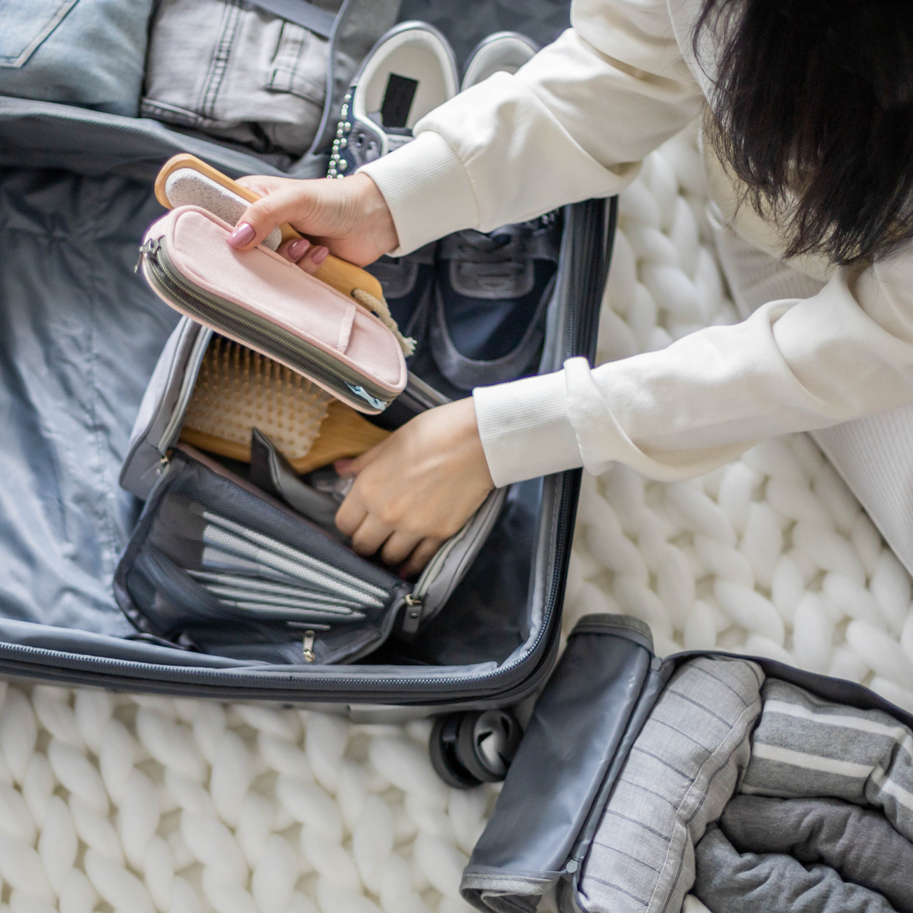 Close-up of a woman packing beauty supplies into a suitcase.