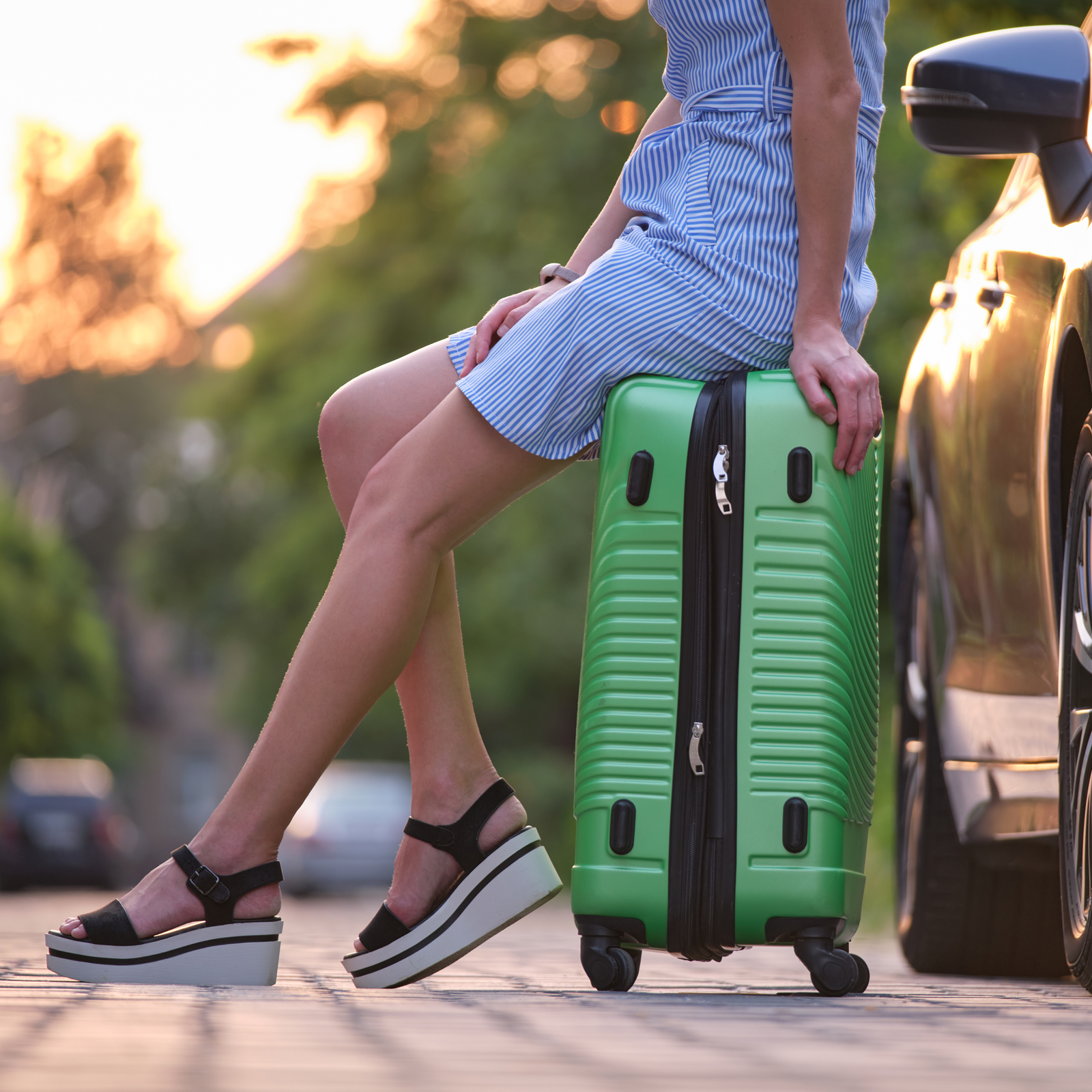 A wman sits on a suitcase stuffed with the contents of a packing list.