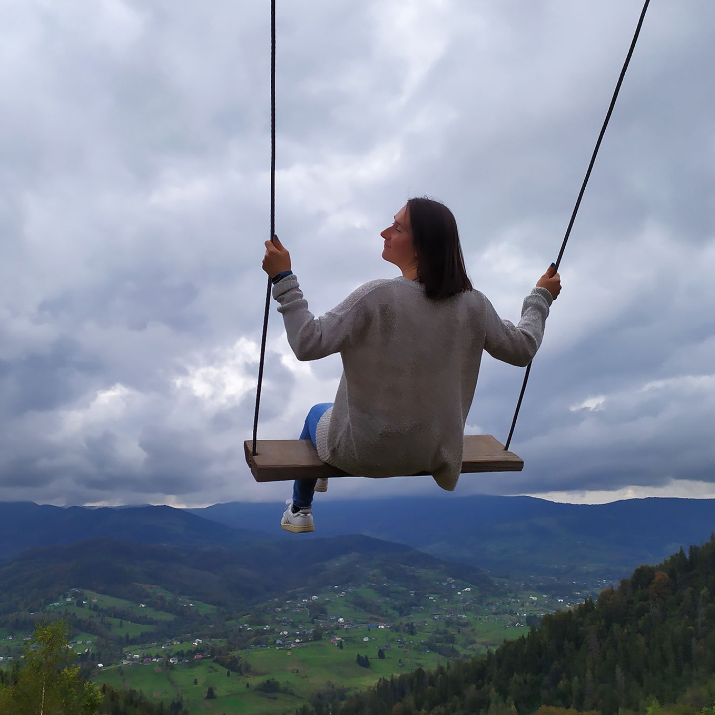 Woman on a swing with a travel landscape in the background.
