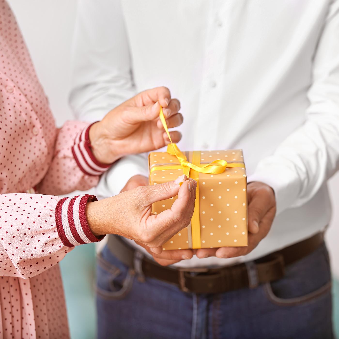 A woman's hands open a gift held by a man in a white shirt.
