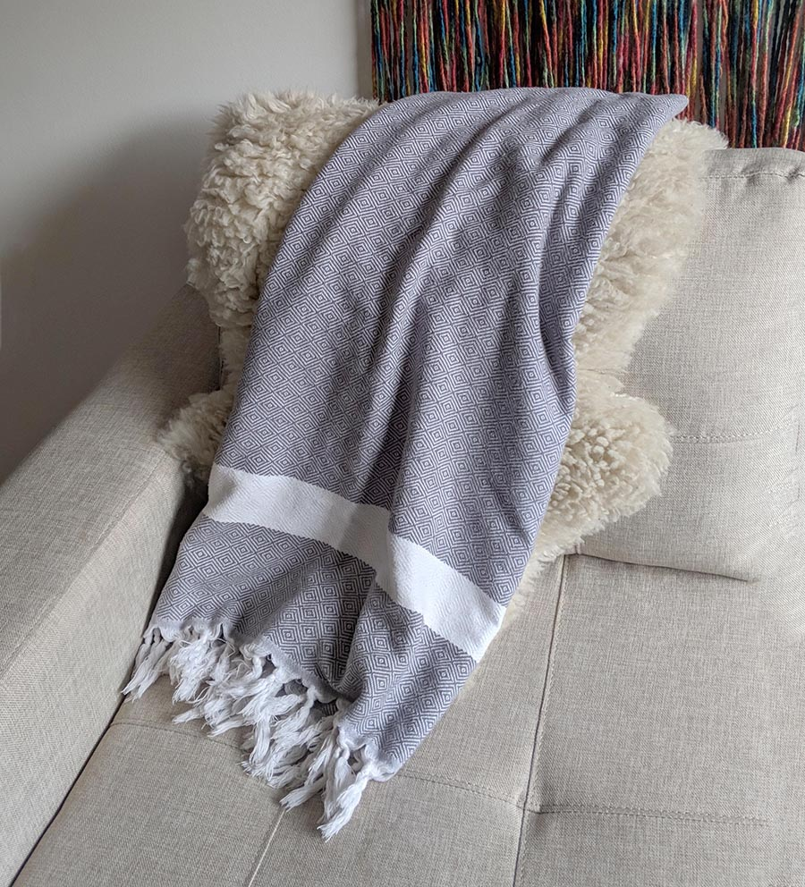A cotton turkish towel draped on a sofa in chile.